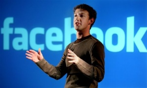 Facebook founder Mark Zuckerberg in front of Facebook Logo